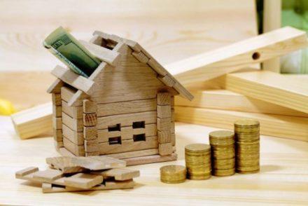 Afbeelding van een houten huisje met geld, ter illustratie van de erfpacht van een woning