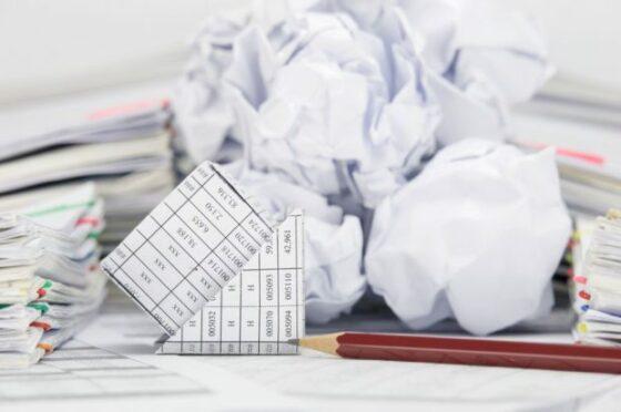Gekreukelde papieren met daarop financiële gegevens en een potlood ernaast