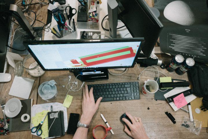 Een rommelig bureau vol met spullen