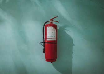 Veiligheid: Een rode brandblusser aan ee blauwe muur